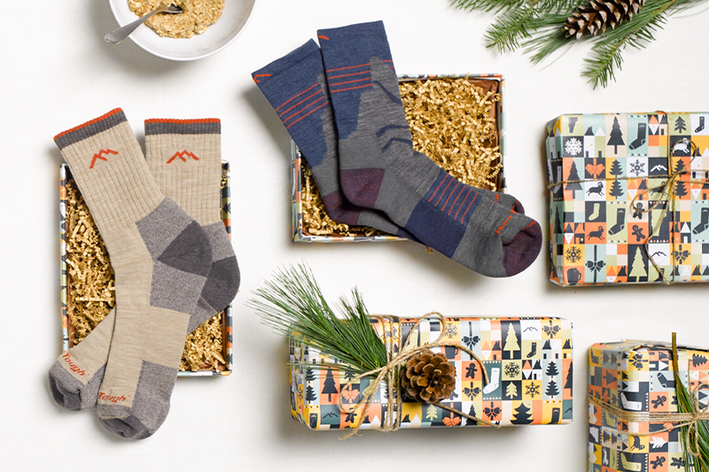 Two men's hiking socks (the perfect gift for him) next to some great holiday wrapping paper