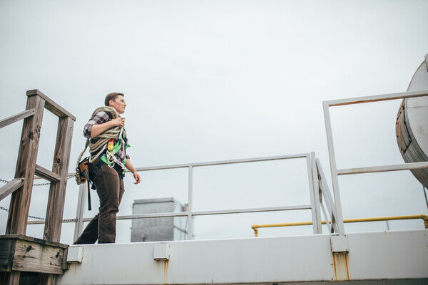 Lady worker walking along rooftop with rope