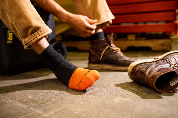 Man tying leather boot laces on over quarter ankle socks for work