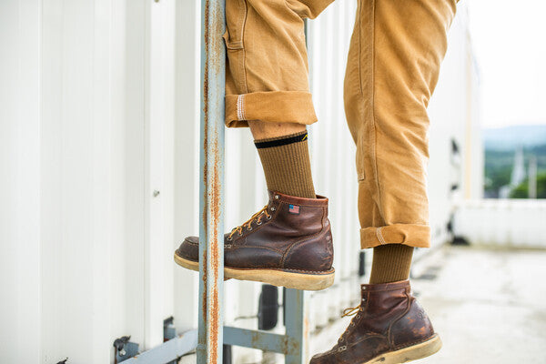 Close up on feet climbing ladder in leather boots and darn tough work socks