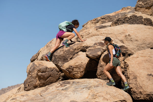 Two friends working together to climb a rock