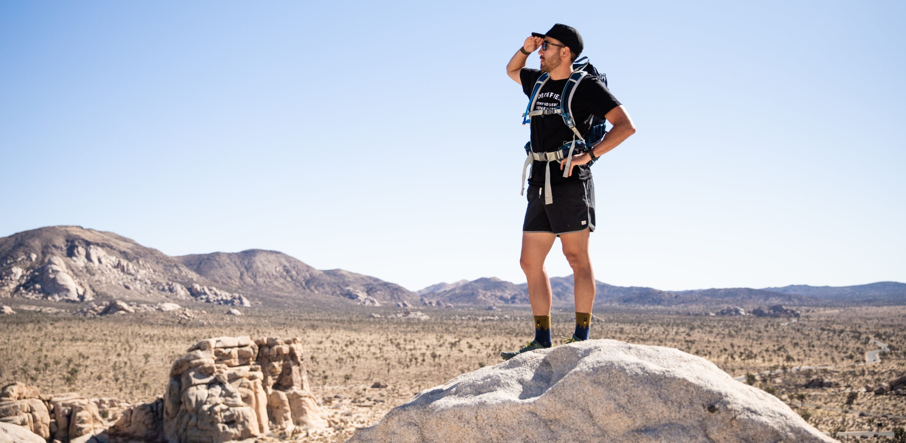 A hiker looking off into the distance for answers to sock questions