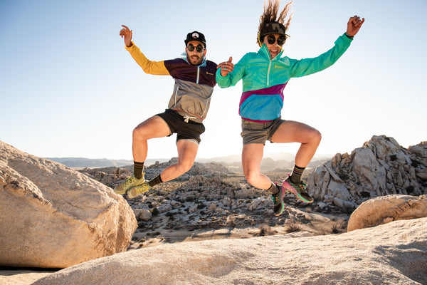 Two people jumping in the air wearing darn tough socks