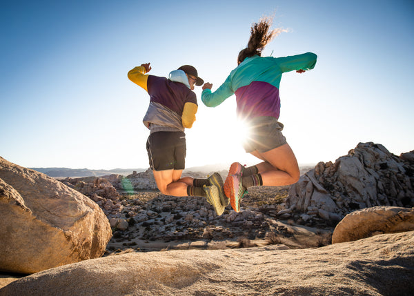 two friends jumping and high fiving with their feet