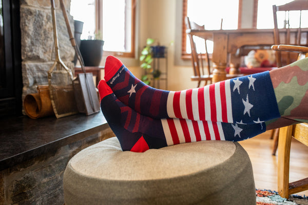 Red white and blue socks on feet by a fireplace