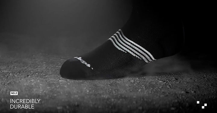 "image of foot with black sock on stepping onto a dark, semi-rough surface with the words ""incredibly durable"" showing."