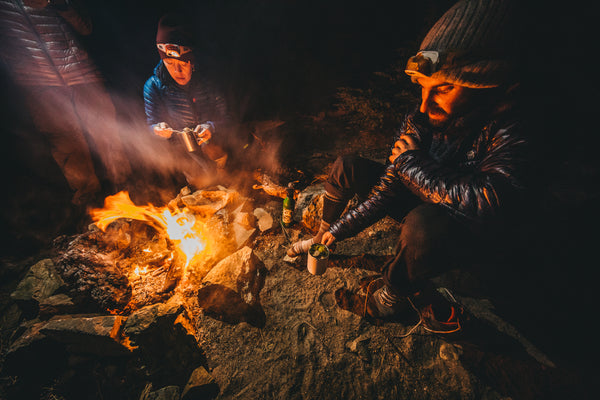 Hikers camped around a fire to stay warm in cold weather