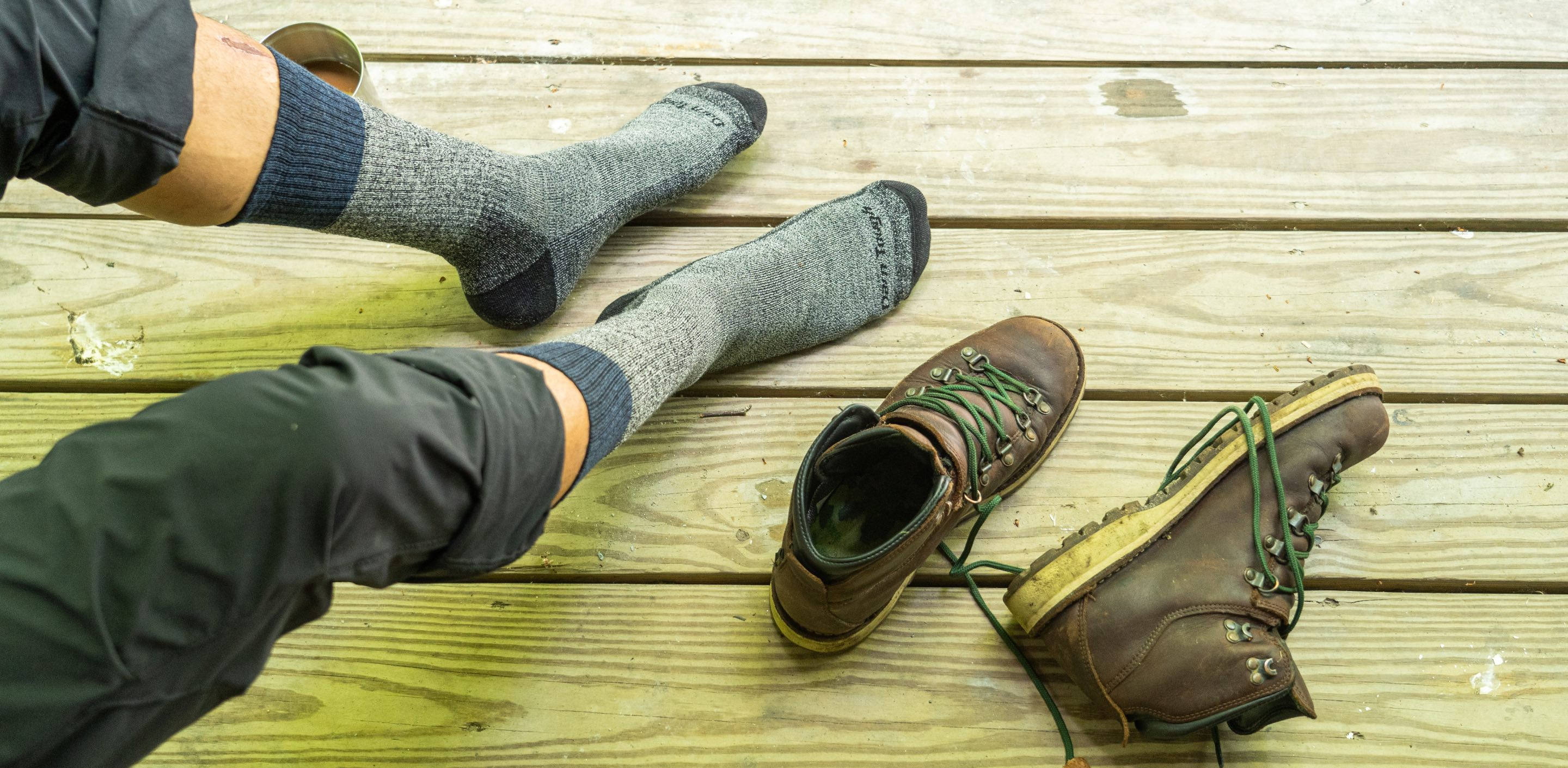 Hiker wondering how to choose socks for hiking with his boots next to him