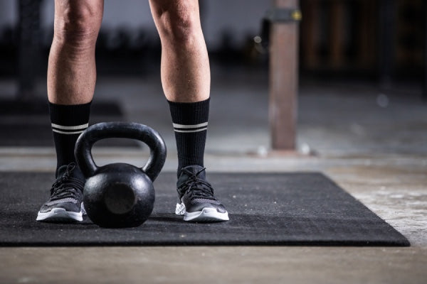 Person at gym working out in darn tough athletic socks