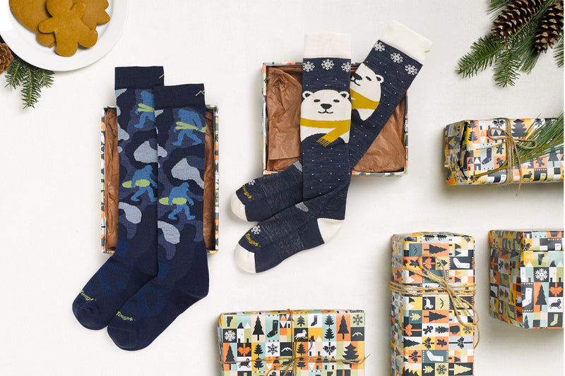 Two of our favorite kids socks laid out with fun holiday wrapping paper, the perfect gift for kids