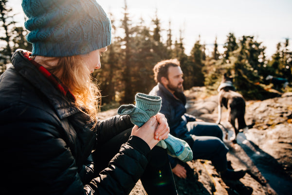 Putting on merino wool hiking socks on a cold winter day