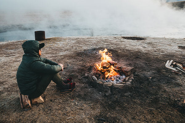Man in merino wool socks by fire, the perfect socks for cold weather