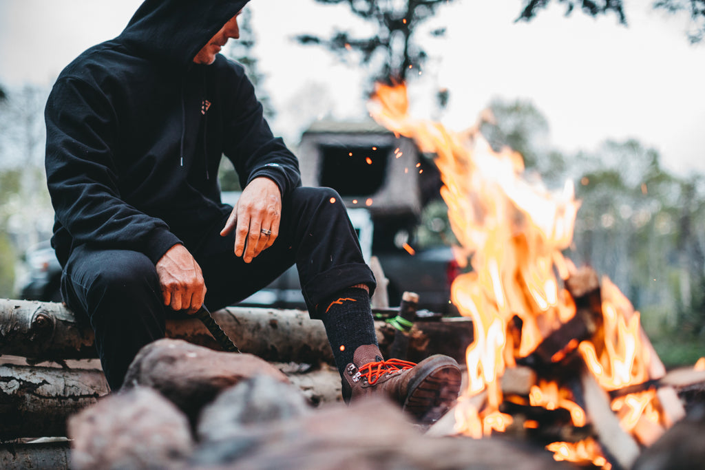 Jeremy Jones sits near campfire, showing his sock by propping a foot up on a large stone.