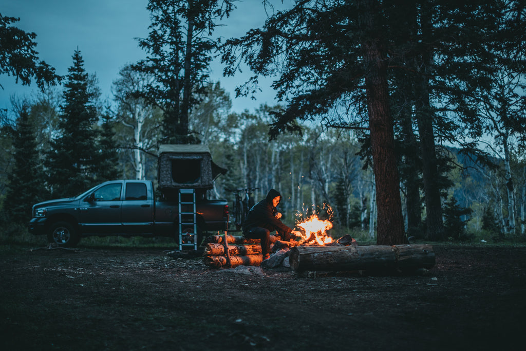 Jeremy Jones sits at his campfire at dusk. His truck and tent are in the background.
