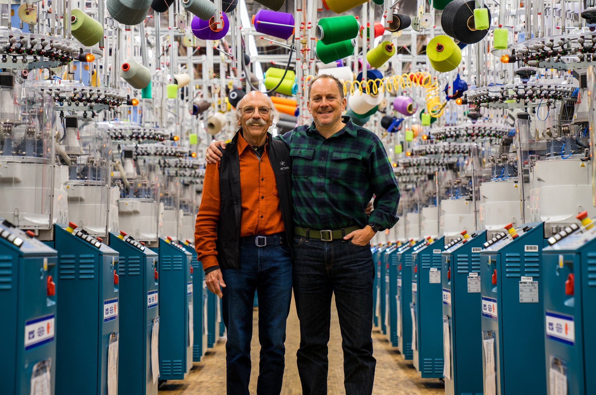 Two men, standing in the knitting room