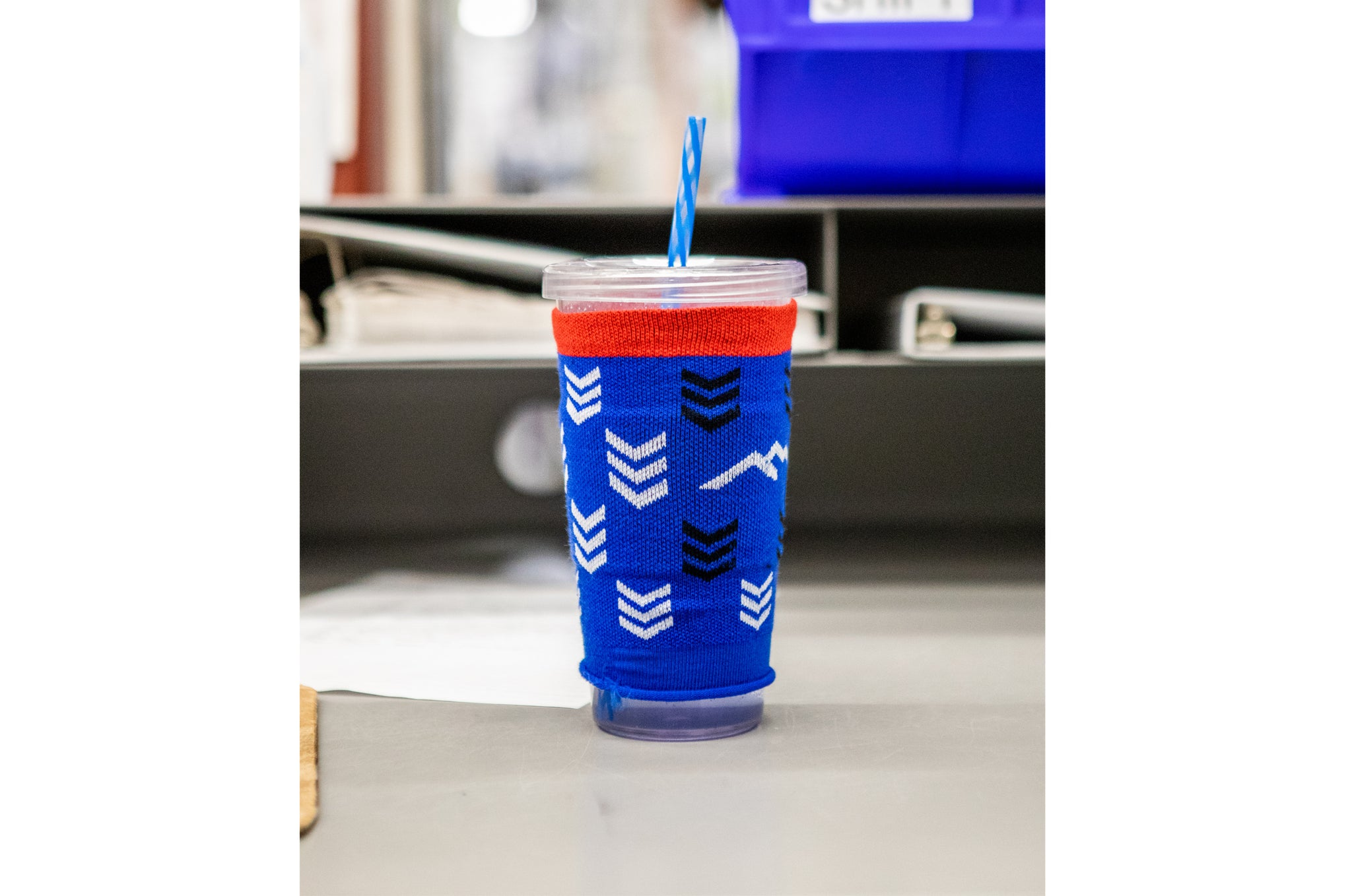 Picture of a drinking cup with a sock being used as a coozie.