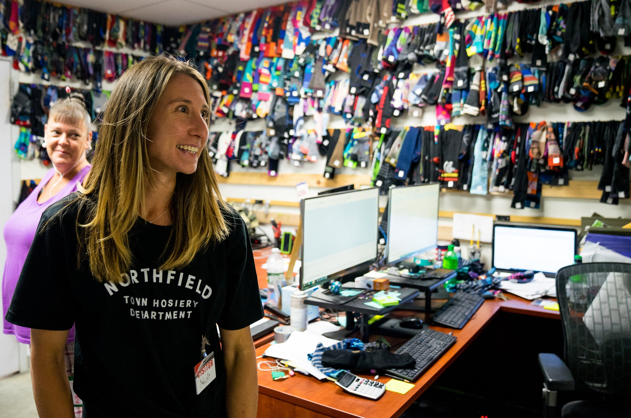 A woman smiles standing in a room where the walls are covered in socks.