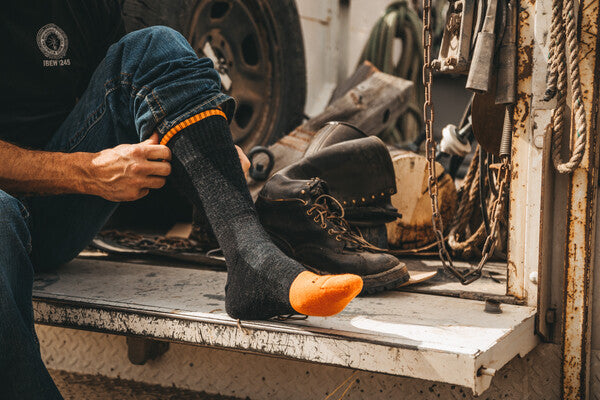 Lineman pulling on darn tough work boot socks, about to put on leather work boots