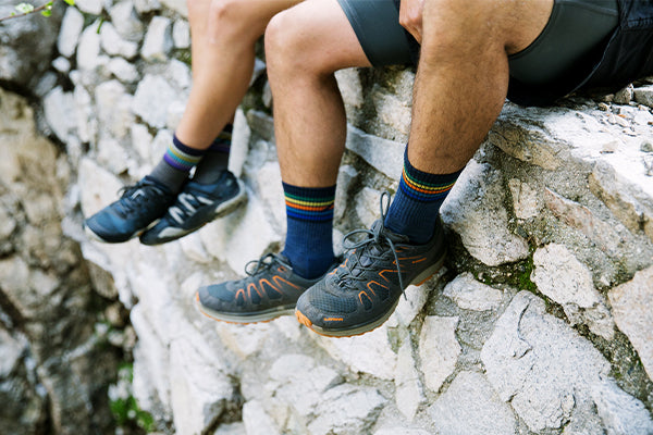 Two hikers wearing darn tough hiking socks seated on rock wall