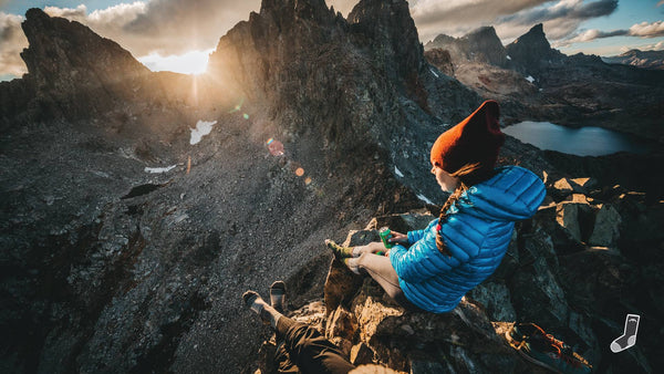 Hiker on summit watching sunset over mountains