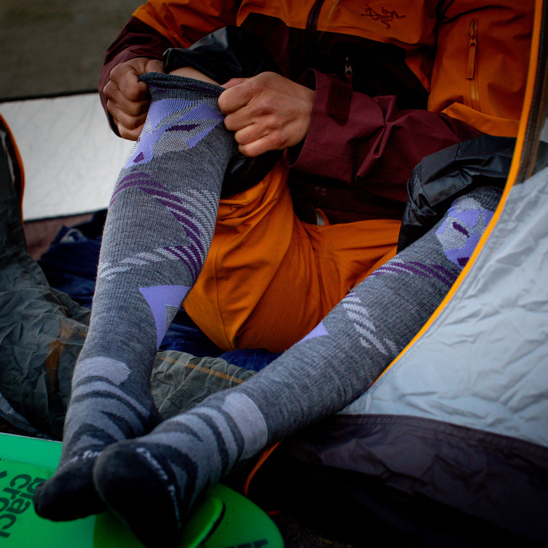 Image of a woman sitting in the opening of a tent, pants rolled up and pulling on her Women's Juniper Over the Calf Midweight Ski & Snowboard Socks in Gray, Lifestyle Image