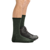 Profile image of male legs facing right wearing Nomad Boot Midweight Hiking Socks in Moss, with back foot also wearing a hiking boot