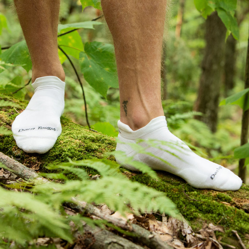 Man standing on log in woods wearing white Coolmax No Show Run socks, Lifestyle Image