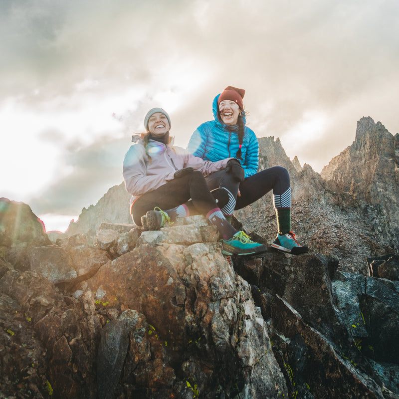 Image of 2 women, laughing, sitting on a rocky mountaintop and one is wearing Women's Bear Town Hiking sock in Purple, Lifestyle Image