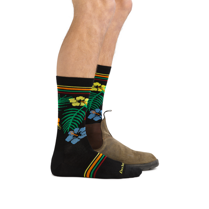 Profile of male legs facing to the right wearing Man standing barefoot wearing Tropic Crew Lightweight Lifestyle Socks in Black and back foot in a casual boot