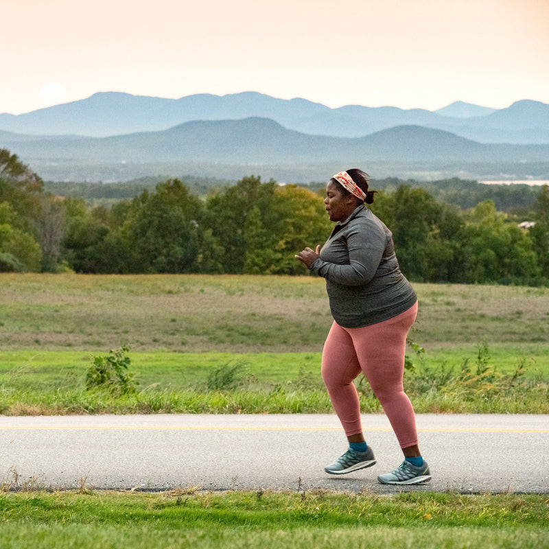 Image of Mirna running along a road with mountains in the background wearing Women's Run 1/4 Running Socks in Baltic, Lifestyle Image