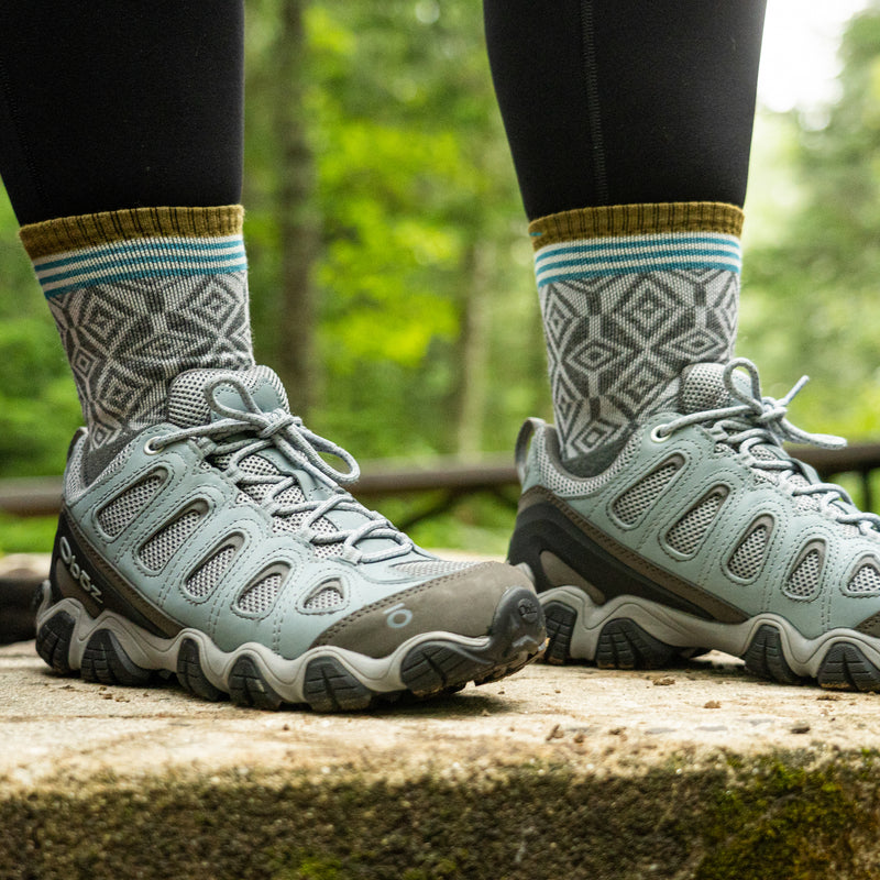 Close up image of a woman's feet wearing sneakers and Women's Sobo Micro Crew Lightweight Hiking Socks in Gray, Lifestyle Image