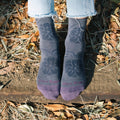 Woman's feet on a log wearing darn tough Mantra casual sock with floral print in slate. Lifestyle Image