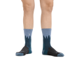 Image of a woman's legs, toes pointed out, wearing Women's Treeline Micro Crew Midweight Hiking Socks in Blue so that the crescent moon on the inside of the calf is visible
