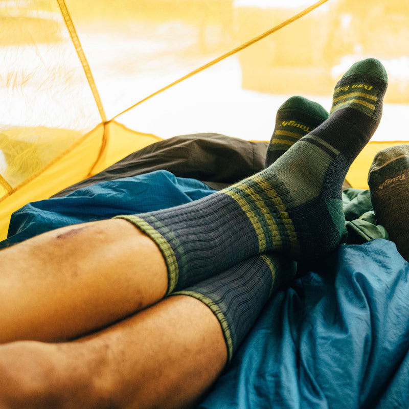 Lifestyle Image of a man's legs, laying down in a tent on top of a sleeping bag, ankles crossed wearing Spur Boot Lightweight Hiking Socks in Denim