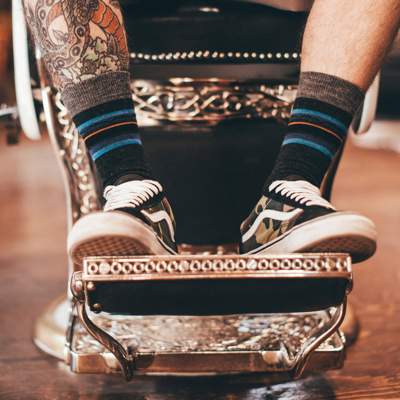 Man sitting in a barber shop chair, wearing sneakers and Whetstone Crew Lightweight Lifestyle socks in Charcoal, Lifestyle Image