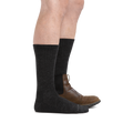 Man standing facing right wearing The Standard Crew  Lightweight Lifestyle Sock in Charcoal wearing a boot on the back foot