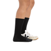 Profile image of a woman's legs on a white background, facing right, wearing Women's Solid Basic Crew Lightweight Lifestyle Sock in Black with one foot also in a casual shoe