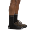 Profile of male legs facing to the right, front foot wearing Hiker Micro Crew Midweight Hiking Sock in Black, foot in back also wearing a hiking shoe