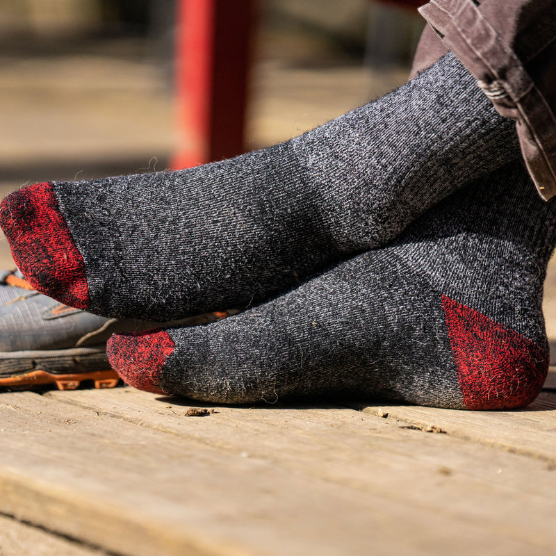 Close up lifestyle image of male feet wearing Mountaineering Over the Calf Heavyweight Hiking Sock in Smoke, Lifestyle Image