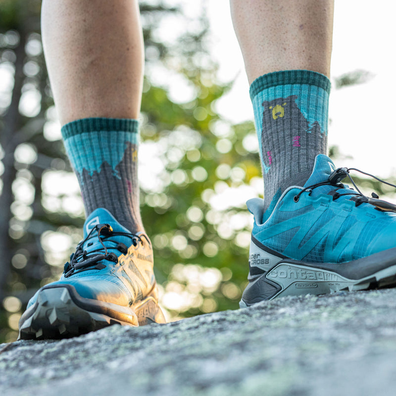 Close up image of a woman's feet, standing on a rock wearing blue sneakers and Women's Bear Town Micro Crew Lightweight Hiking Socks in Aqua, Lifestyle Image