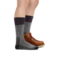 Profile image of a woman's legs on a white background, facing right, wearing Women's Scout Boot Midweight Hiking Socks in Plum with one foot in a hiking boot