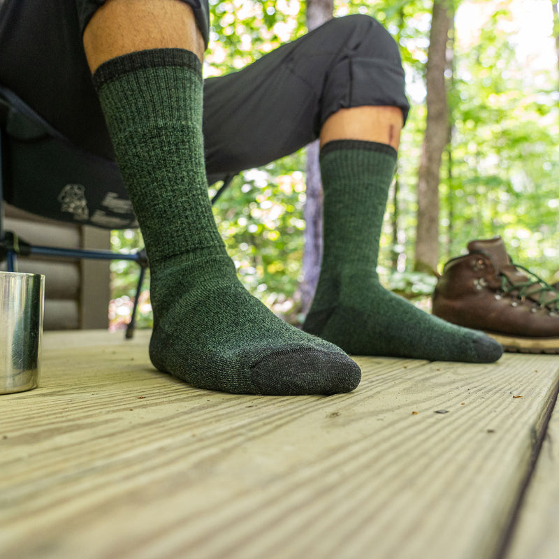 Close up lifestyle image of a man's feet while sitting in a camping chair on a porch, hiking boots nearby wearing Nomad Boot Midweight Hiking Socks in Moss, Lifestyle Image