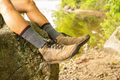 Feet hanging off rock wearing hike shoes and darn tough men's hiker boot socks style 1403 in charcoal, Lifestyle Image