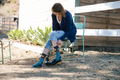 Woman seated in chair in backyard putting shoes on over the Animal Haus micro crew socks with foxes on them, Lifestyle Image
