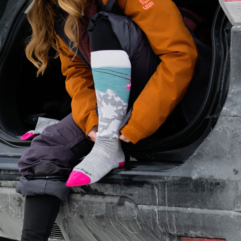 Woman sitting in the open back of her car, wearing snow pants and pulling on her Women's Yeti Over the Calf Ski & Snowboard Socks in Glacier, Lifestyle Image