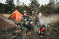 Three hunters at base camp getting ready to set out by pulling on Darn Tough hunting socks. Lifestyle Image