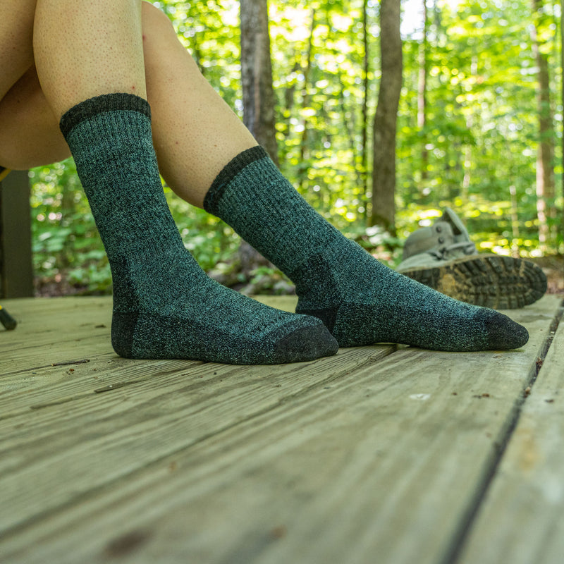 Image of a woman's feet on a wooden porch in the woods, hiking boots in the background, wearing Women's Nomad Boot Midweight Hiking Socks in Aqua, Lifestyle Image