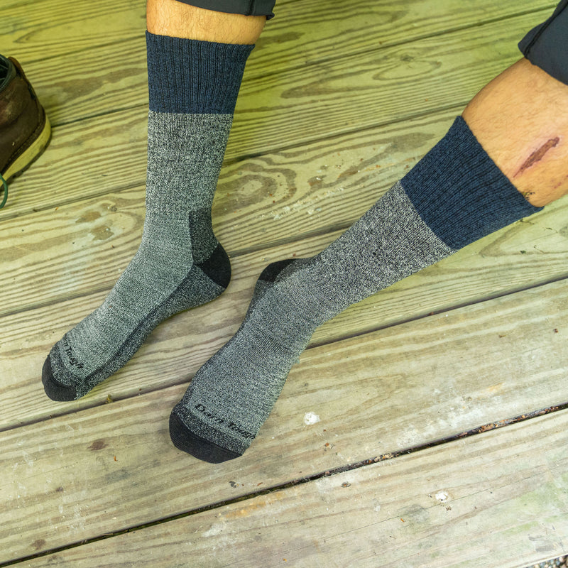 Lifestyle image shot looking down at a man's feet on a wooden deck, wearing Scout Boot Midweight Hiking Socks in Denim, Lifestyle Image
