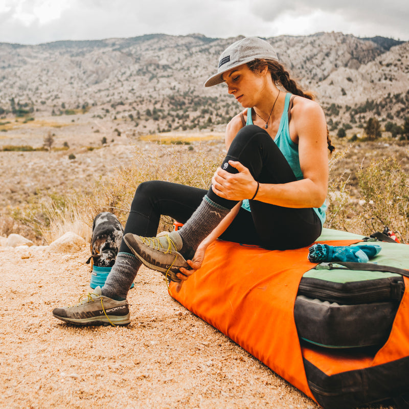 Image of a woman at her campsite in the desert, taking off her hiking shoes and wearing Women's Hiker Boot Midweight Hiking Socks in Slate, Lifestyle Image