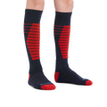 Kid standing barefoot wearing Edge Over the Calf Midweight Ski & Snowboard socks in Eclipse